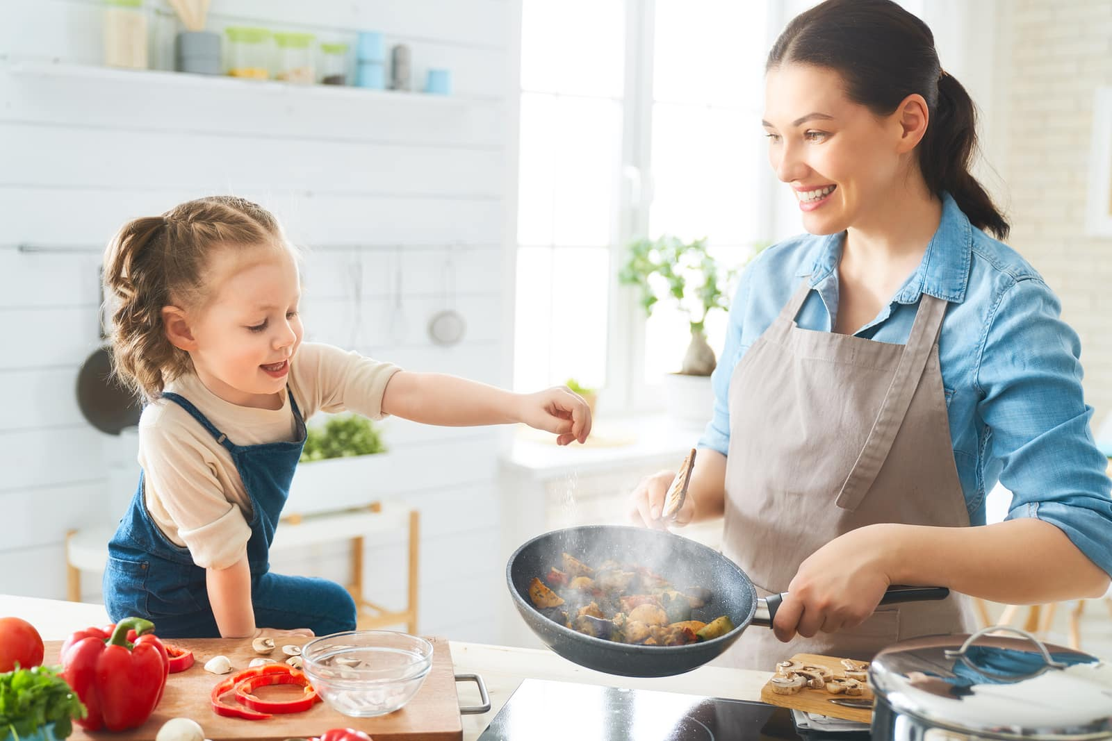 How to beat Thanksgiving bloat- skip snacks but not meals. Woman and daughter cooking