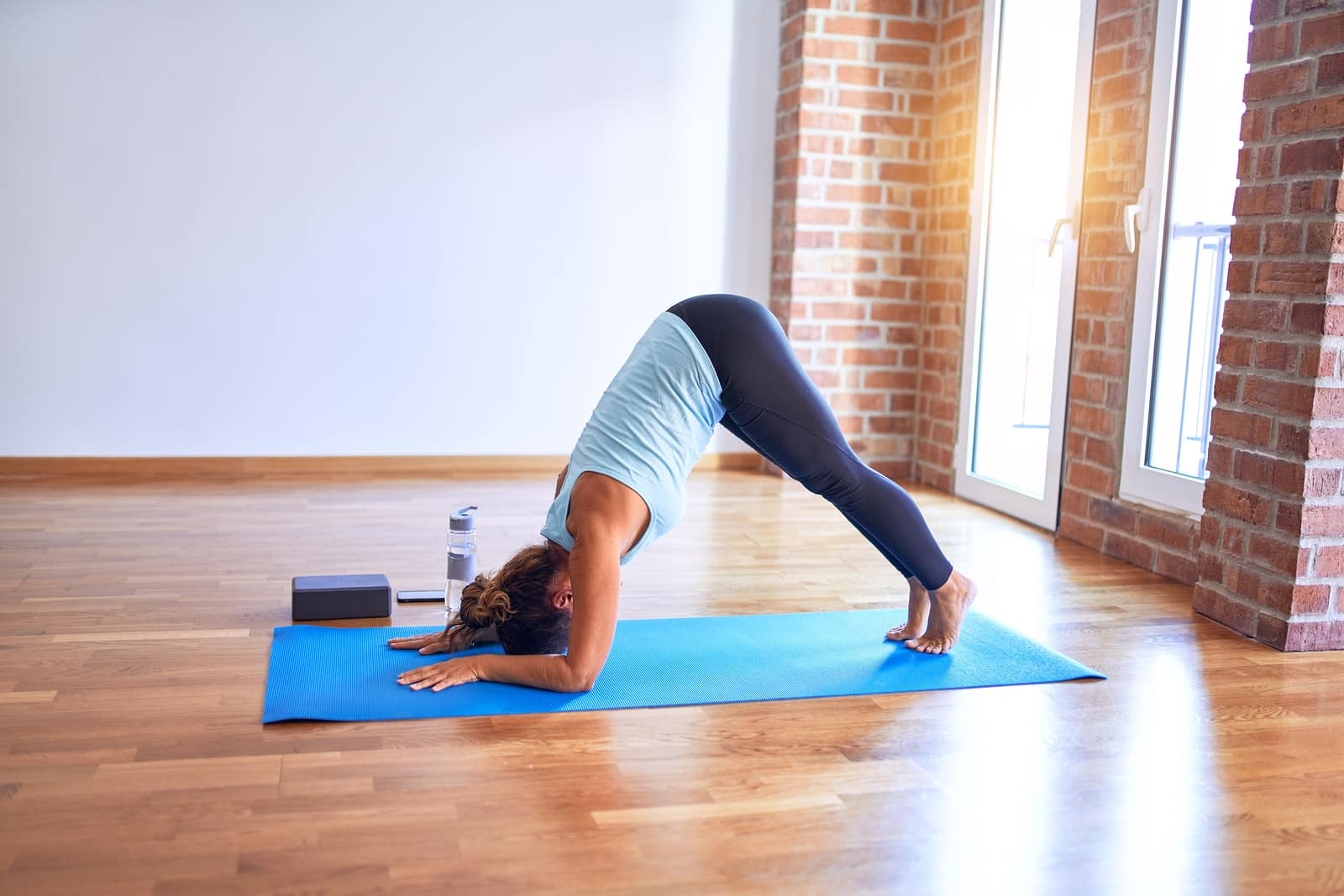 Woman doing dolphin pose for hormonal insomnia