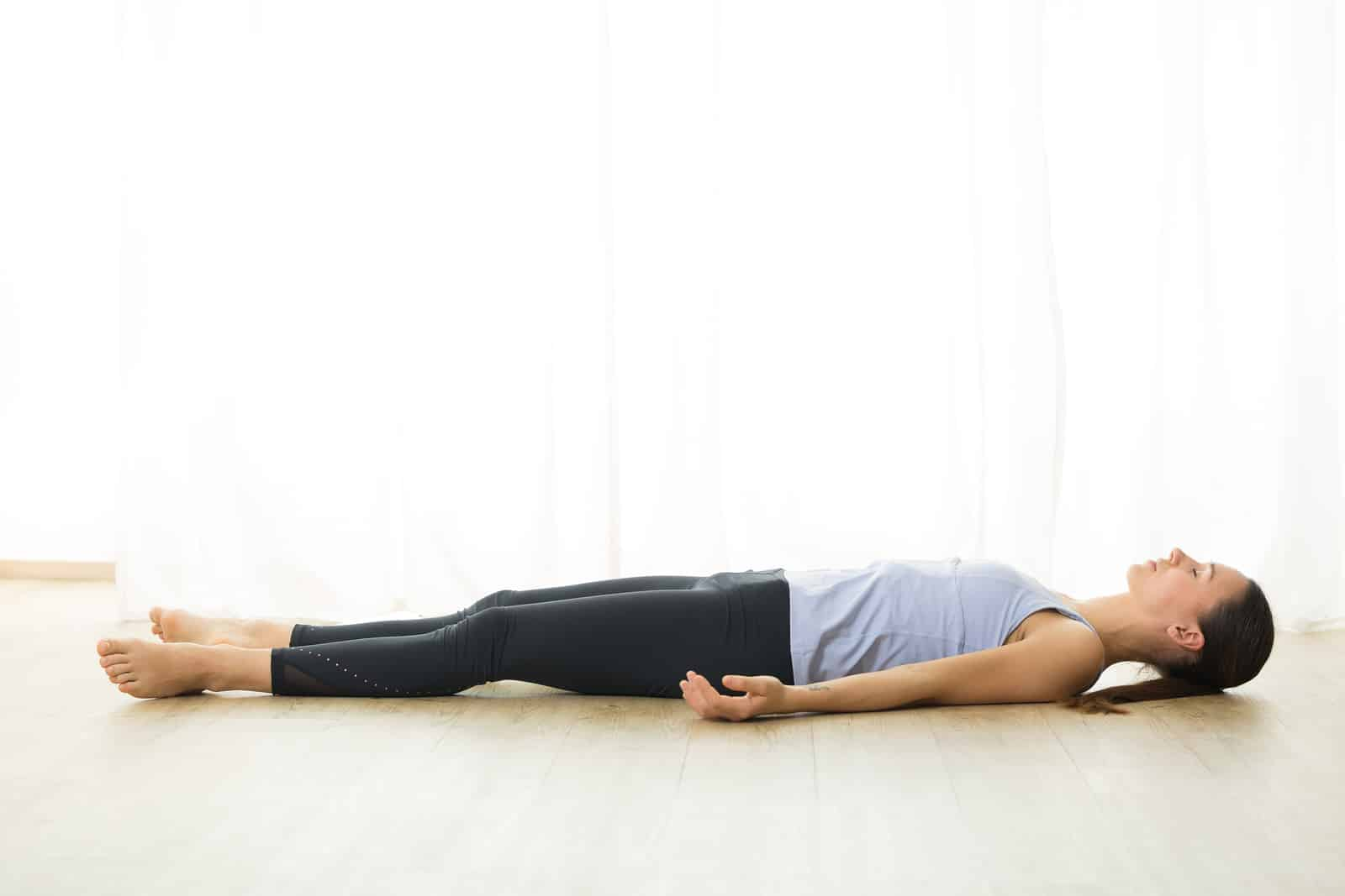 Woman doing savasana for hormonal insomnia relief