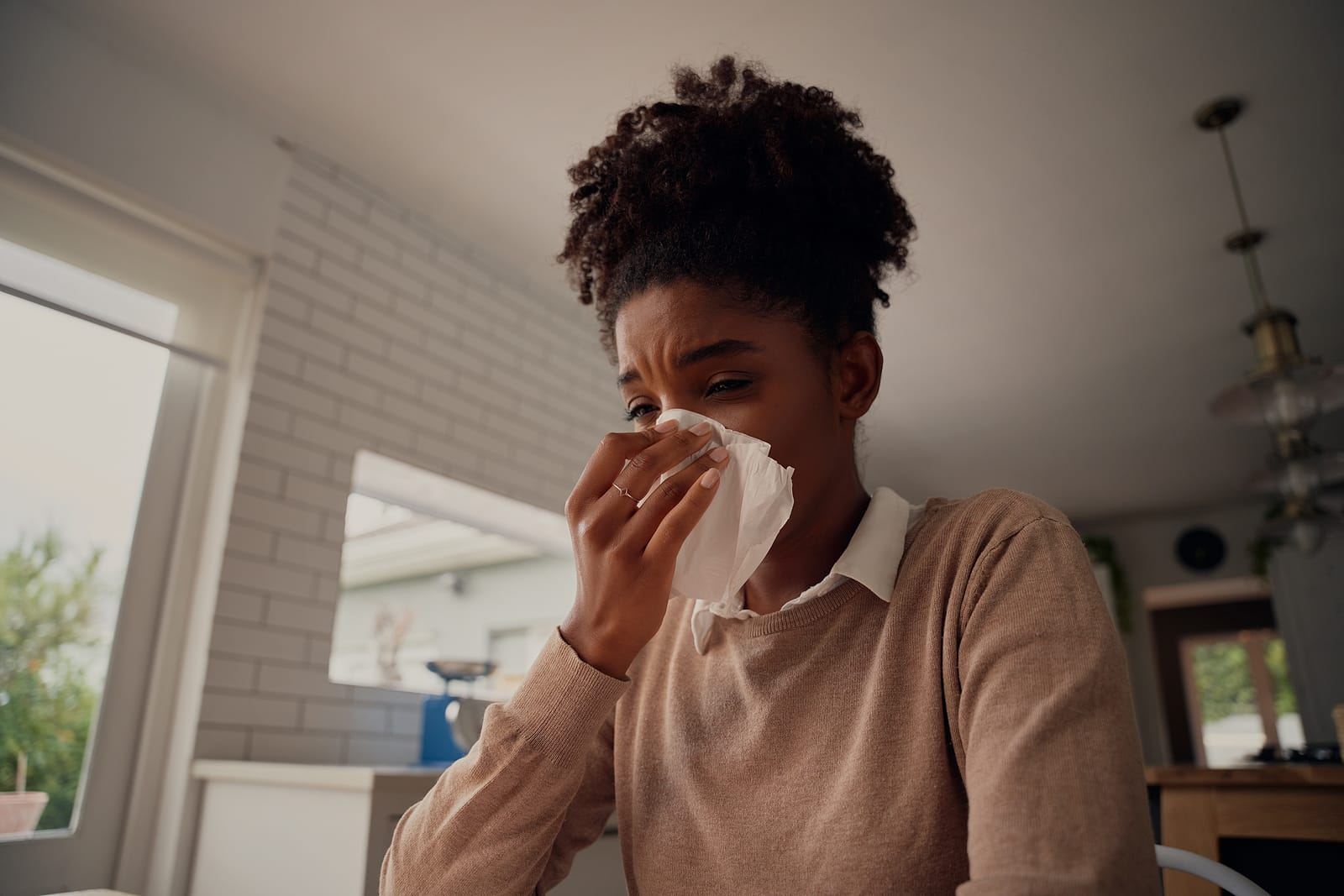 Woman feeling sick while sitting at table