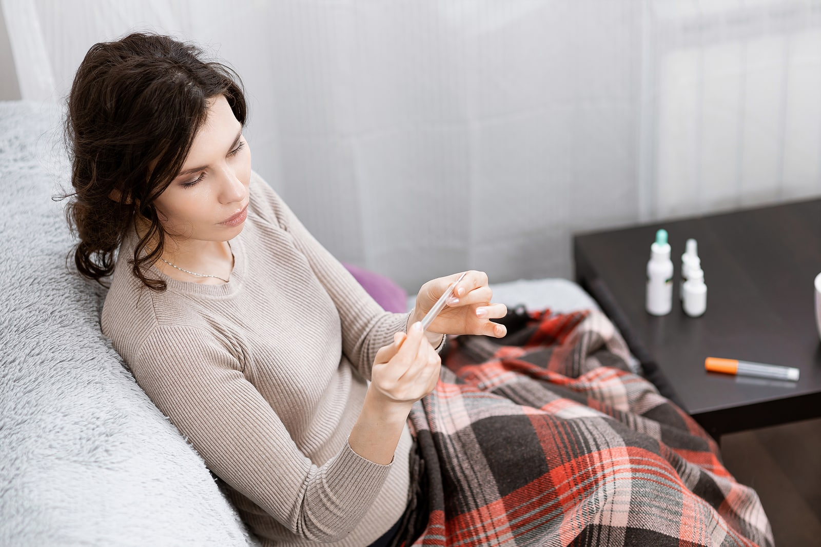 Woman feeling sick at home taking temperature