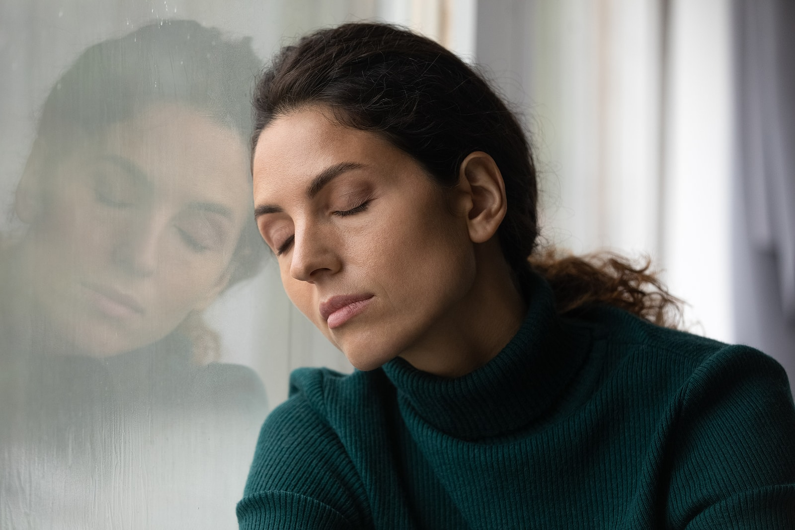 Can emotional stress cause pelvic pain and affect mental health- woman lonely and leaning against window