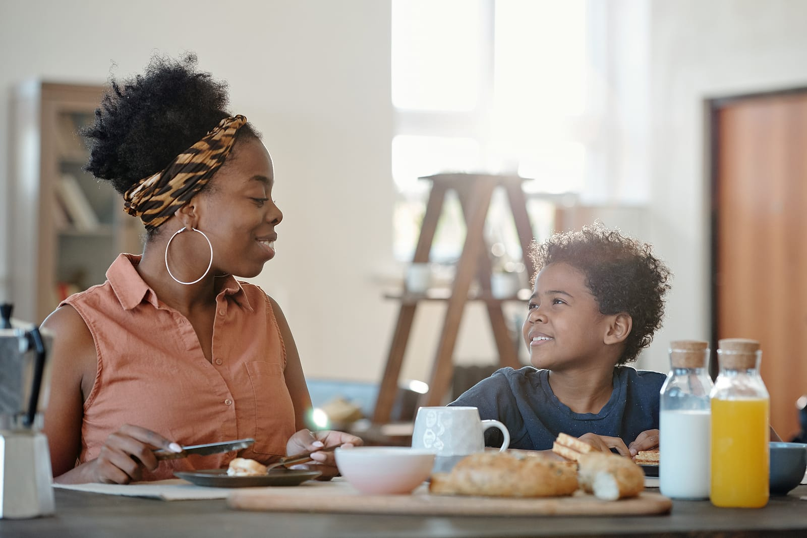 Woman eating breakfast at table with son.