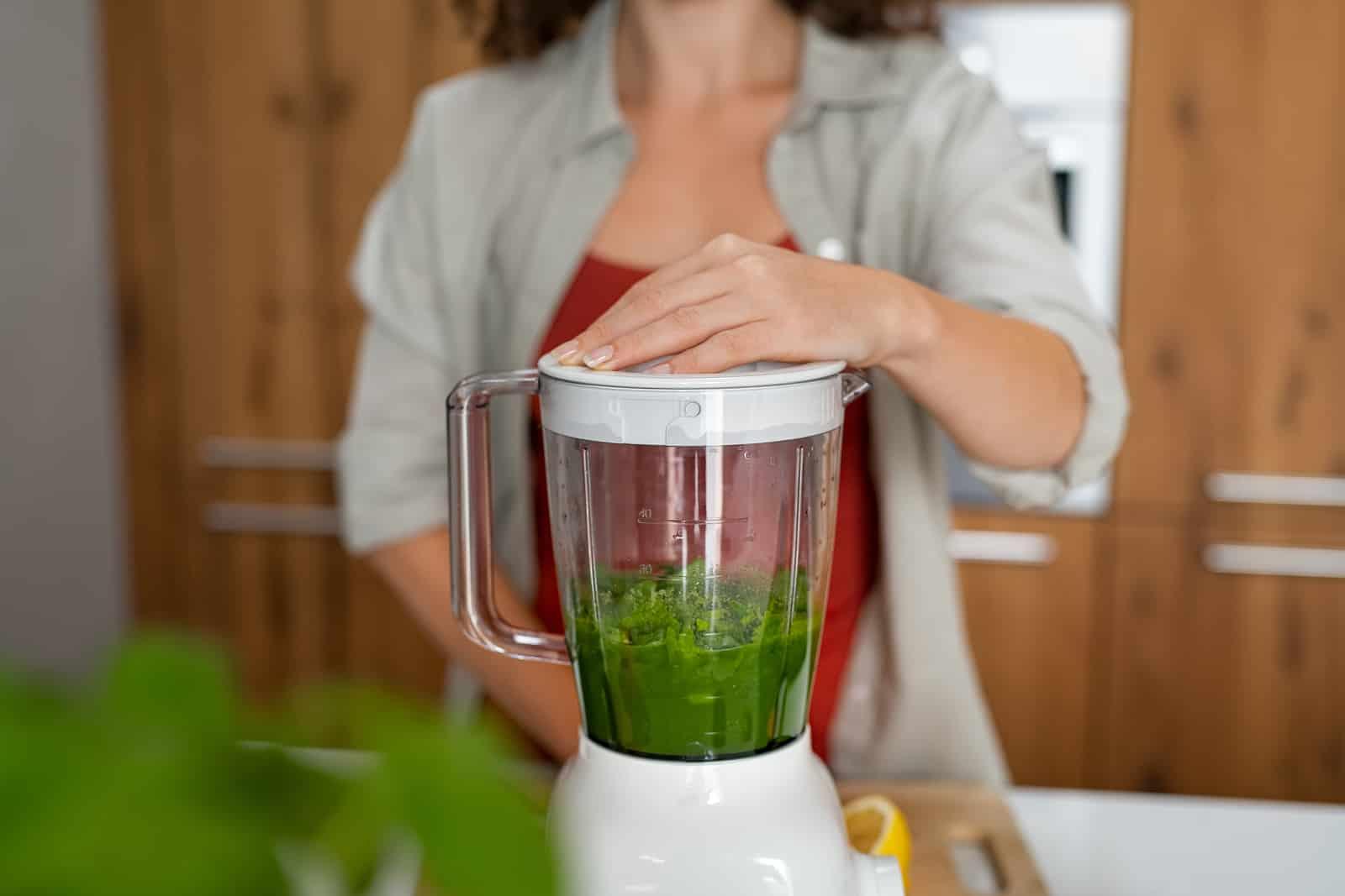 Woman making green smoothie