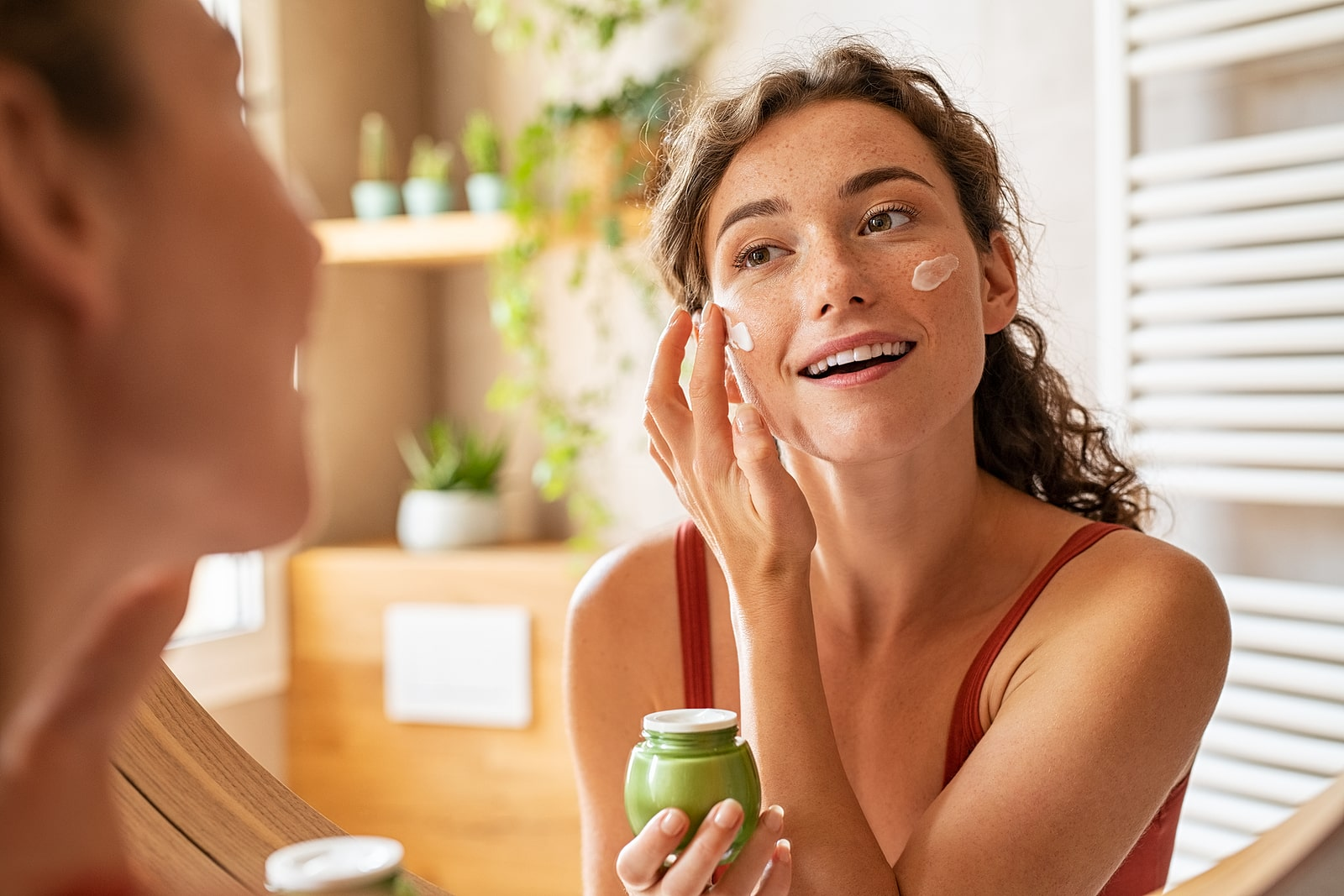 How toxins affect fertility- cosmetics. Woman putting on face lotion in mirror