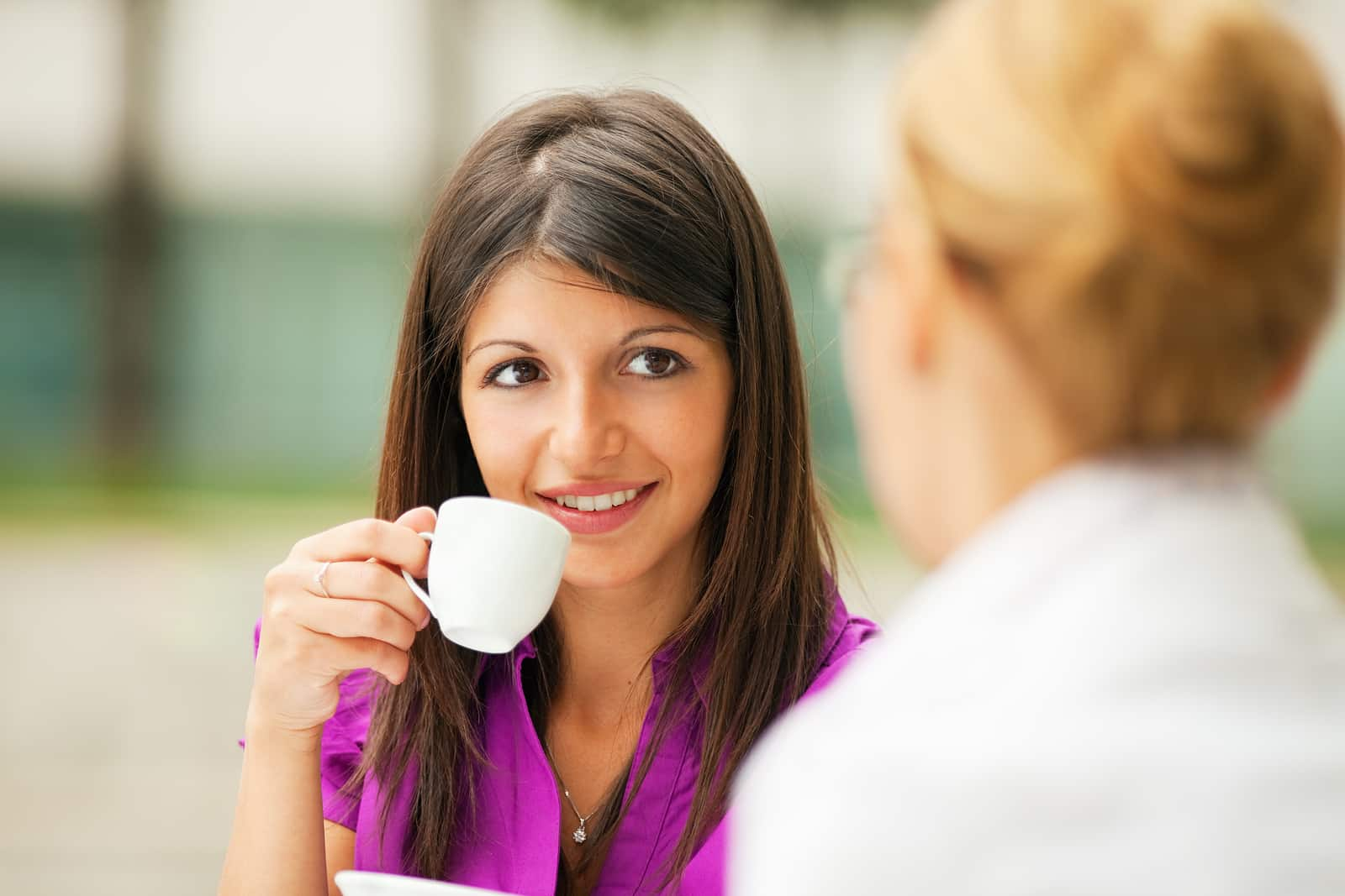Why am I always tired? Woman having espresso outdoors with a friend
