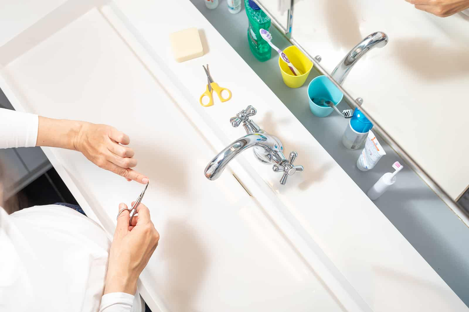 Hormones and nail growth- woman standing at sink using nail products for home manicure