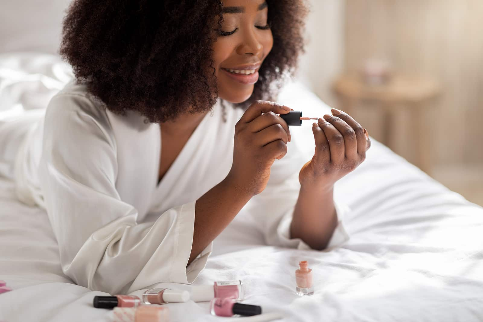 Hormones and nail growth- woman laying on bed in white robe giving herself a manicure