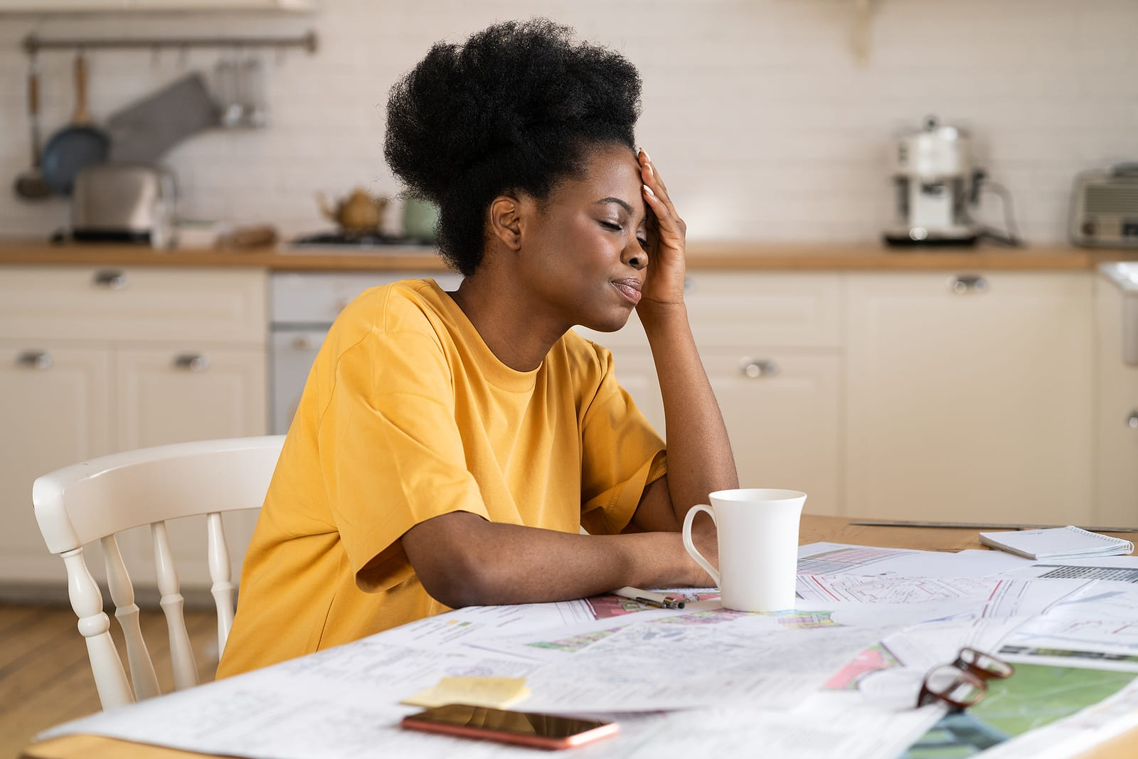 Woman sitting at kitchen table with coffee. Hand on head and stressed