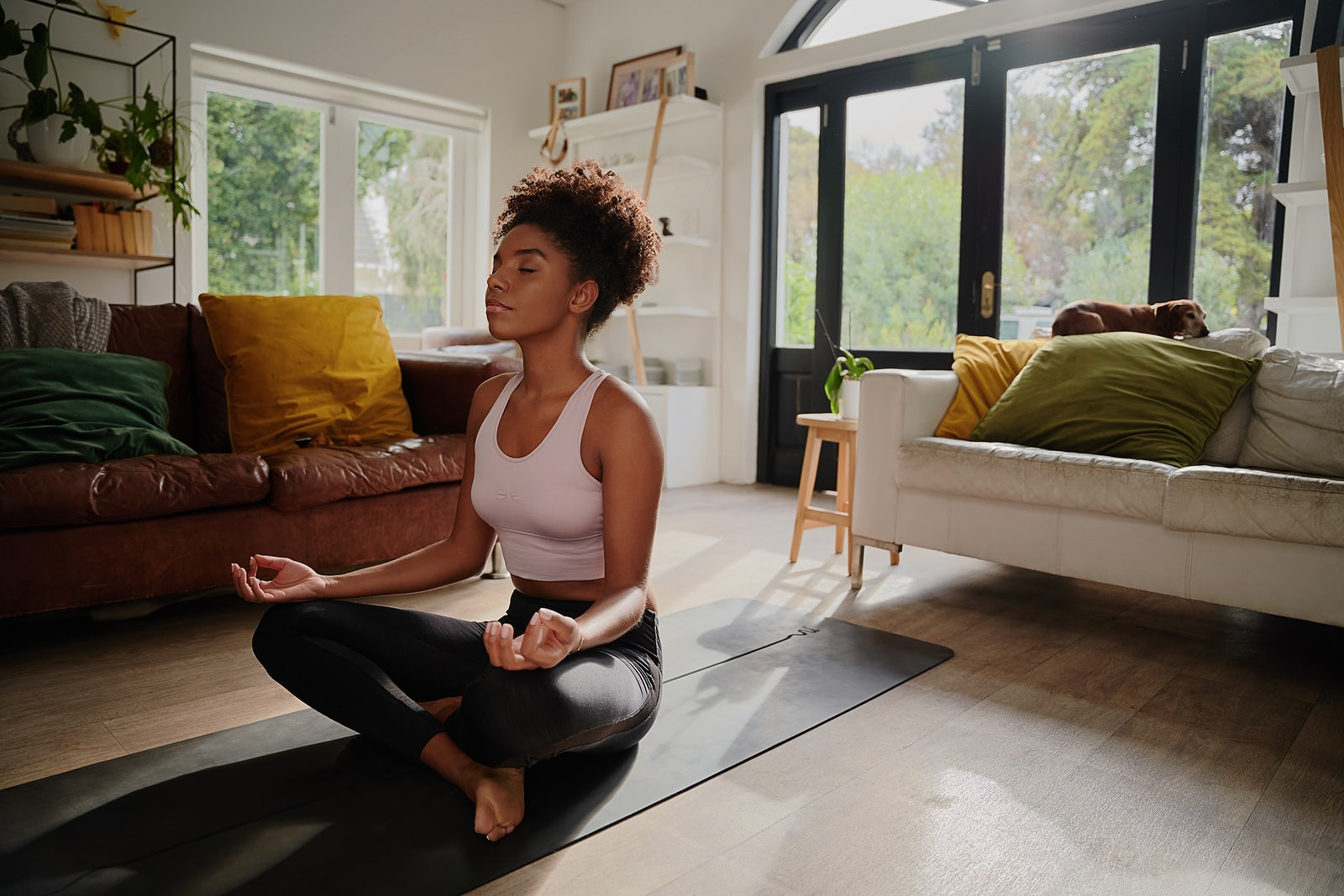 Yin yoga for hormones- african american woman sitting in lotus pose at home