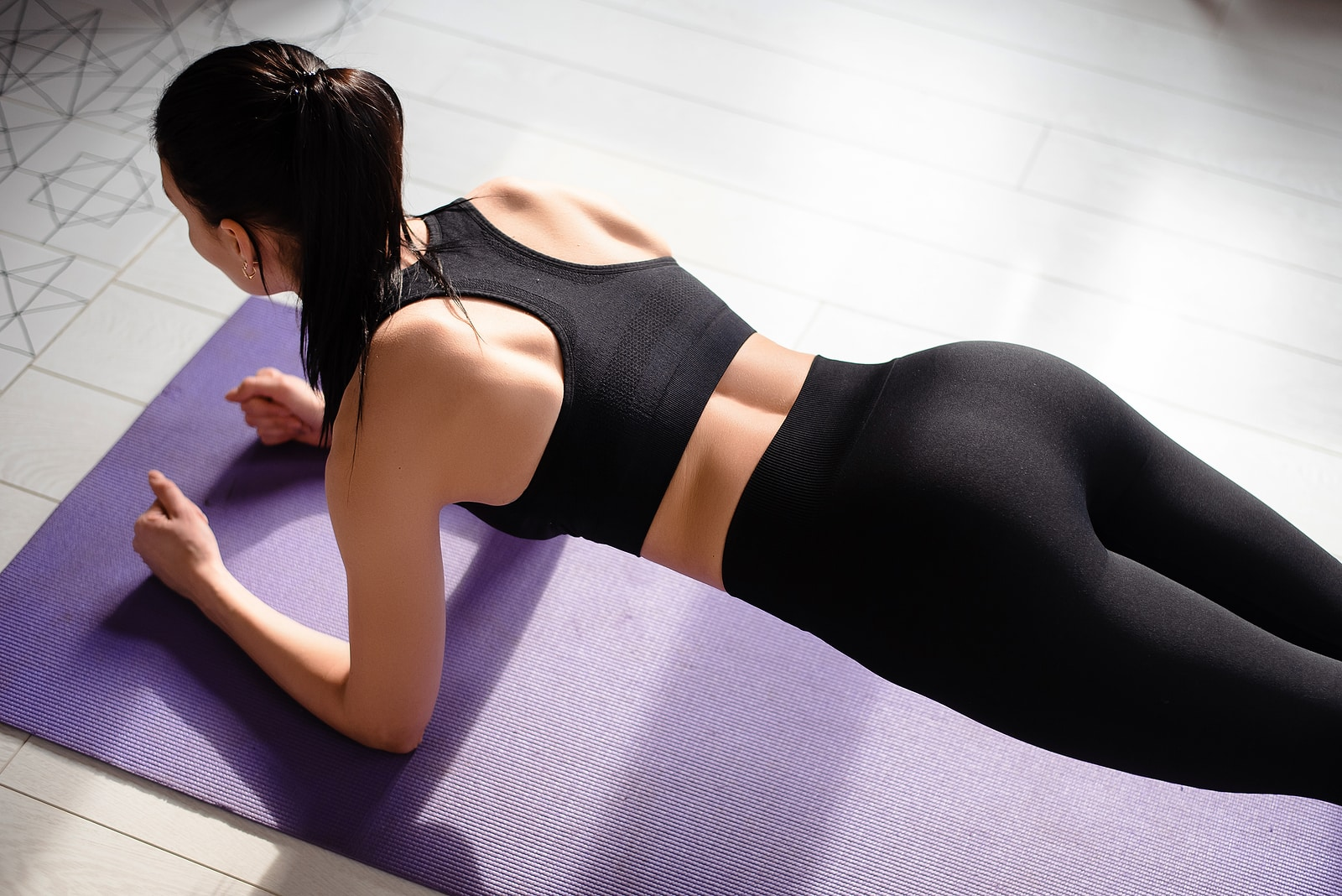 Yin yoga for hormones- woman doing yoga pose in black workout gear